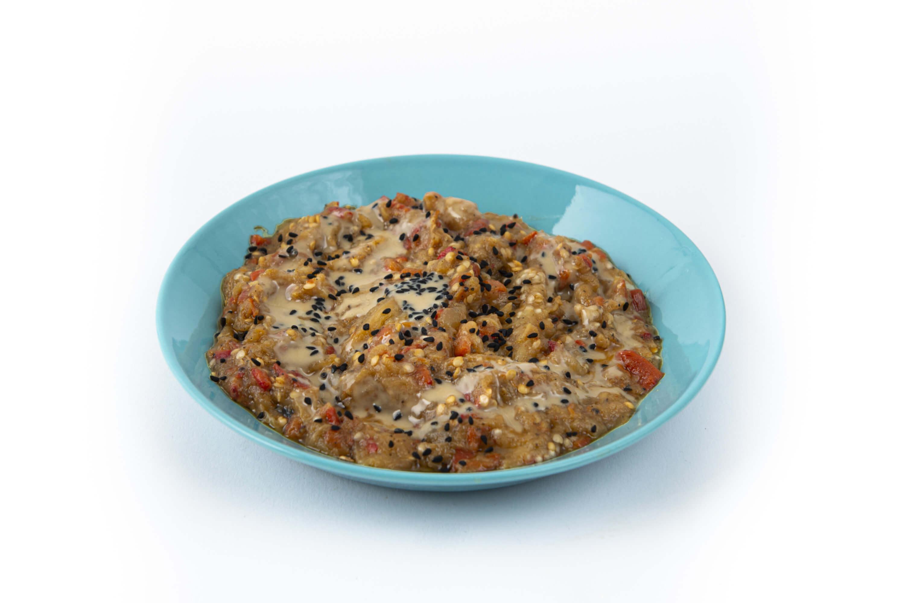 Geräucherte Aubergine mit Tahin auf einem Teller